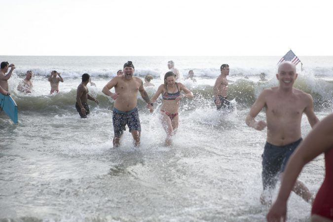 Participants of the the 2020 polar bear plunge in Margate, NJ come out of the water after jumping in on Wednesday, January 1, 2020. (Miguel Martinez for WHYY)