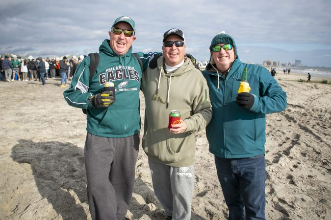 Brothers Brendan, Kevin, and Bill Bradley (from left) pose for a picture during the the 2020 polar bear plunge in Margate, NJ on Wednesday, January 1, 2020. (Miguel Martinez for WHYY)