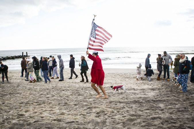 Teddy Costa run with a flag in front of the crow during the 2020 polar bear plunge in Margate, NJ on Wednesday, January 1, 2020. (Miguel Martinez for WHYY)
