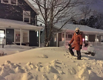 Caitrin Dunn stands on her  buried car in Monmouth County's Avon. (Photo courtesy of Jennifer Husar)