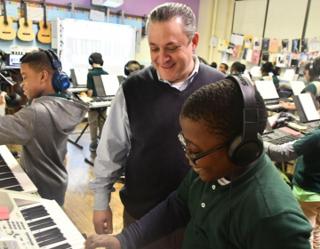 Music teacher Marc Dulberg watches as Amir Newsome plays the keyboard in class. (Abdul Sulayman/The Philadelphia Tribune)
