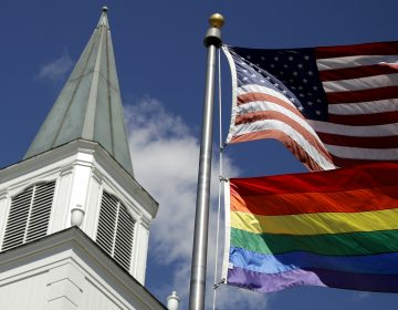 A rainbow gay pride flag flies below the U.S. flag last year in front of the Asbury United Methodist Church in Prairie Village, Kan. (Charlie Riedel/AP Photo)