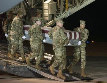 An Air Force team moves a transfer case containing the remains of one of the young sailors killed after a Saudi military student opened fire at a Pensacolanaval base last month. (Cliff Owen/AP Photo)