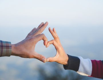 A couple makes a heart shape with their hands