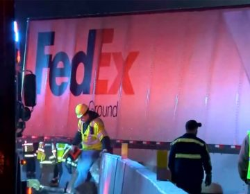 Workers in vests near a crashed FedEx truck after a fatal accident on the Pennsylvania Turnpike. (NBC Philadelphia)