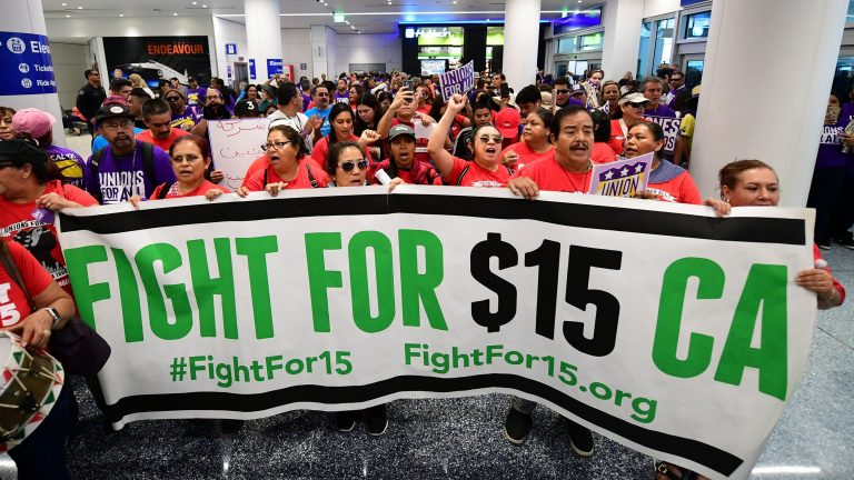 Airport employees, Uber and Lyft drivers, and other workers protest for a $15 minimum wage at Los Angeles International Airport in October. Increases in minimum wages contributed to bigger pay gains for lower-income workers. (Frederic J. Brown/AFP via Getty Images)
