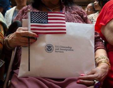 A newly sworn-in U.S. citizen holds the U.S. flag and paperwork during a 2018 naturalization ceremony in New York City. (Bryan R. Smith/AFP via Getty Images)