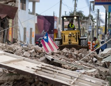 A Puerto Rican flag waves on top of a pile of rubble as debris is removed from a main road in Guánica. (Ricardo Arduengo/AFP via Getty Images)