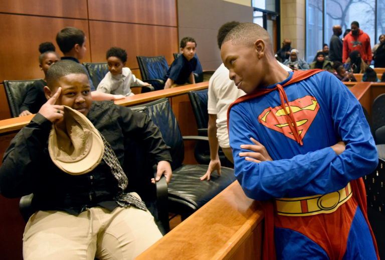 During a mock trial at Rutgers Law School, Superman, played by Nuri Waheed, banters with juror Corey Livingston-Randall, left, before the verdict is announced. (April Saul for WHYY)