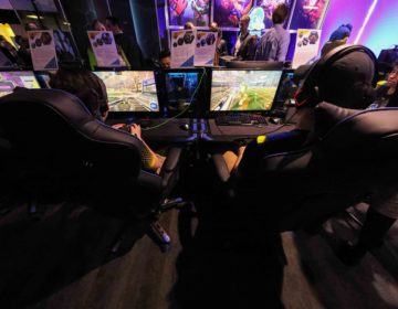 Two players are seen from behind their chairs at an esports arena