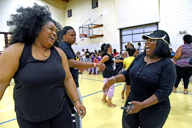 Tawanda Jones, right, and daughter LaQuicia Charnell, left; laugh at the Michael J. Doyle Fieldhouse gym during a sleepover sponsored by the Camden Sophisticated Sisters in June 2019.  (April Saul for WHYY)