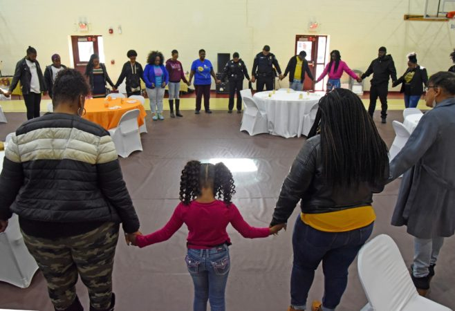 In November 2019, Tawanda Jones, leads attendees in prayer at the Michael J. Doyle Fieldhouse gym during a building shower to celebrate the Camden Sophisticated Sisters making a new home there.  (April Saul for WHYY)