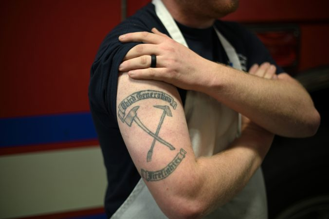 Thrid generation firefighter AJ Alves, 25, shows his tattoo as he poses for a photo at Humane Fire Co., in Pottsville, Pa. (Bas Slabbers for Keystone Crossroads)