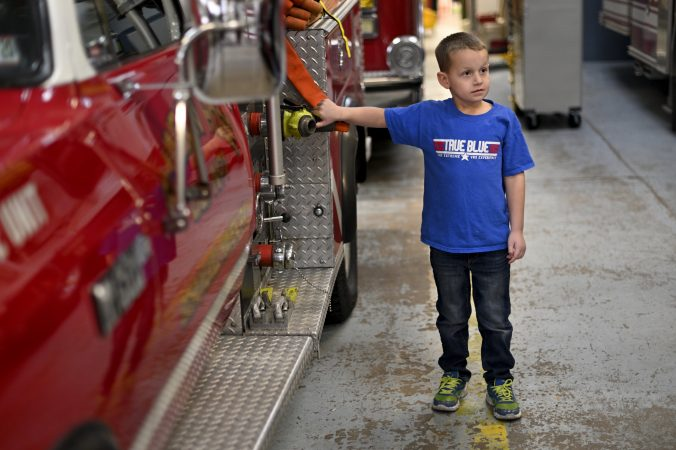 Tyler Donnatti, 6, son of the local fire chief, grandson of Gloria, stands next to the brush truck of Rainbow Hose Co., in Schuylkill Haven, Pa. (Bas Slabbers for Keystone Crossroads)