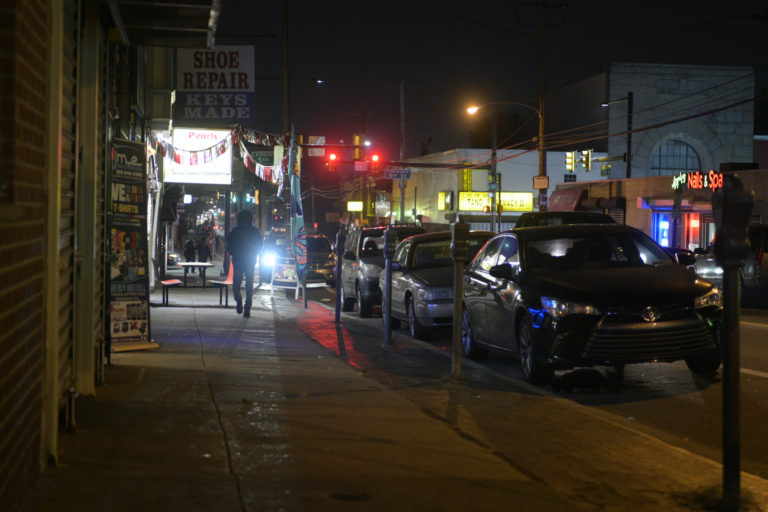 People stroll past shops as they close for the night at the commercial corridor on the 5500 block of North Fifth Street on Tuesday. (Bastiaan Slabbers for WHYY)
