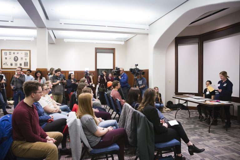 Fourteen Iowa residents partake in a satellite Iowa caucus at the University of Pennsylvania on February 3, 2020. The group ultimately assigned two delegate votes to Bernie Sanders, one to Elizabeth Warren, and one to Pete Buttigieg. (Rachel Wisniewski for WHYY)