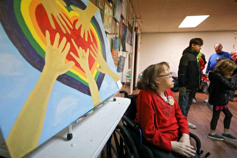 Artist Danielle Fangman is seen near her painting, 'Family Love,' during an art therapy exhibit on Feb. 10, 2020, at The Art Studio in Wilmington, Del. (Saquan Stimpson for WHYY)