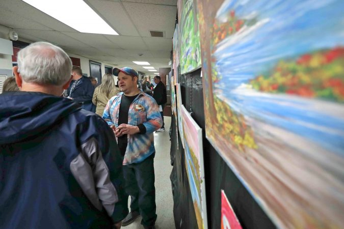 David Turner (center) speaks with attendees about his paintings during an art therapy exhibit on Feb. 10, 2020, at The Art Studio in Wilmington, Del. (Saquan Stimpson for WHYY)