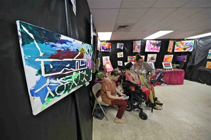 Haley Shiber (center) is seen surrounded by her paintings during an art therapy exhibit on Feb. 10, 2020, at The Art Studio in Wilmington, Del. (Saquan Stimpson for WHYY)
