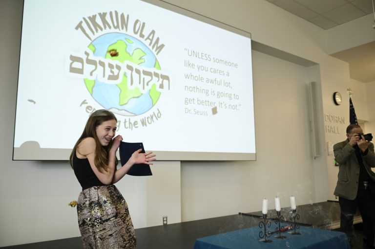 Sophie Mills braces for candy throws during her bat mitzvah ceremony at Jewish Children's Folkshul in Philadelphia. Family and friends gathered to see the seventh-grader give a presentation on five inspirational women who repaired the world. (Bastiaan Slabbers for WHYY)