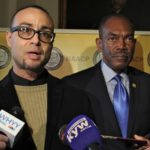 The NAACP has announced that it has filed suit on behalf of Robert Holbrook (left) and other currently and formerly incarcerated people whose Census numbers apply to the community where they are incarcerated rather than where they live. Holbrook spoke during a press conference at City Hall, accompanied by Philadelphia NAACP President Rodney Muhammad (right). (Emma Lee/WHYY)