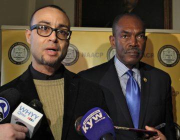 The NAACP has filed suit on behalf of Robert Holbrook (left) and other currently and formerly incarcerated people whose Census numbers apply to the community where they are incarcerated rather than where they live. Holbrook spoke during a press conference at City Hall, accompanied by Philadelphia NAACP President Rodney Muhammad (right). (Emma Lee/WHYY)