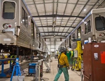 Two Market-Frankford Line cars lifted for repairs at the 69th Street SEPTA repair shop. (Kimberly Paynter/WHYY)