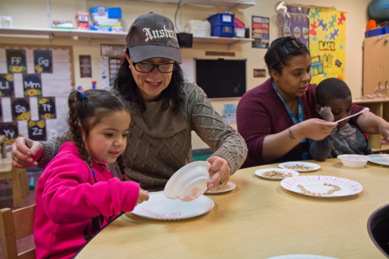 Kids in SPIN's autism support preschool classroom work on their motor skills by creating a marshmallow fluff and Cheerio heart craft project. (Kimberly Paynter/WHYY)