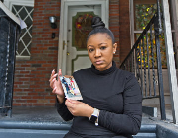 Sakeenah Benjamin holds a photo of her cousin Manny, who was shot and killed in her West Philly neighborhood when she was 10 years old. (Kimberly Paynter/WHYY)
