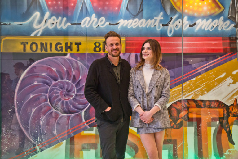 """""""Dispatches From Elsewhere"""" stars Eve Lindley (right) and Jason Segel (left) pose with local street artist Jimmy McMenamin's new mural at the Comcast Center. (Kimberly Paynter/WHYY)"""