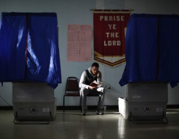 Election worker Khalid Battle reads a book as he waits for voters to cast their ballots in Pennsylvania primary election at Memorial Gospel Crusades Church, Tuesday, April 24, 2012, in Philadelphia. Voters in New York, Connecticut, Delaware, Rhode Island and Pennsylvania were heading to the polls on Tuesday for primary elections. (AP Photo/Matt Rourke)