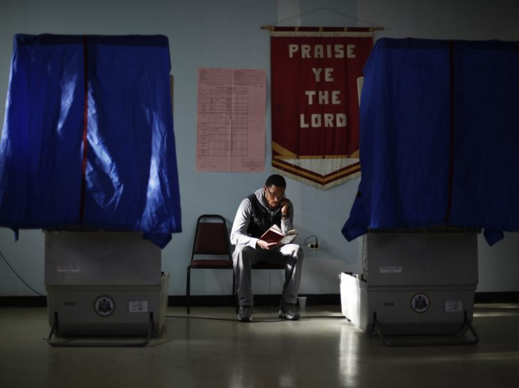 Election worker Khalid Battle reads a book as he waits for voters to cast their ballots in Pennsylvania primary election at Memorial Gospel Crusades Church in Philadelphia. (AP Photo/Matt Rourke)