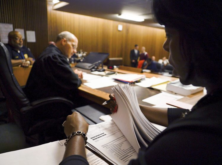 In this Aug. 30, 2017, photo, Stephanie Pope-Earley, right, sorts through defendant files scored with risk-assessment software for Jimmy Jackson Jr., a municipal court judge, on the first day of the software's use in Cleveland. In a growing number of local and state courts, including Cleveland, judges are now guided by computer algorithms before ruling whether criminal defendants can return to everyday life, or remain locked up awaiting trial. (Dake Kang/AP Photo)