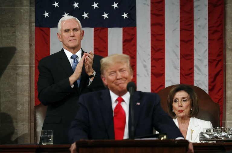 U.S. Vice President Mike Pence stands and applauds as Speaker of the House Nancy Pelosi reacts to President Donald Trump as he delivers his State of the Union address. (REUTERS/Leah Millis/POOL)
