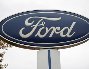 FILE - In this Oct. 20, 2019, file photo, the company logo stands over a long row of unsold vehicles at a Ford dealership in Littleton, Colo. (AP Photo/David Zalubowski, File)