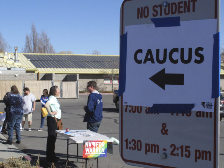 Volunteers for various campaigns talk to voters as they enter a presidential caucus site at Mendive Middle School in Sparks, Nevada on Saturday, Feb. 22, 2020. (Scott Sonner/AP Photo)