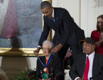 "FILE-In this Tuesday, Nov. 24, 2015 photo, Willie Mays, right, looks on as President Barack Obama presents the Presidential Medal of Freedom to NASA mathematician Katherine Johnson during a ceremony in the East Room of the White House, in Washington. Johnson, a mathematician on early space missions who was portrayed in film ""Hidden Figures,"" died Feb. 24, 2020. (AP Photo/Evan Vucci)"