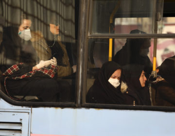 Woman, wearing face masks, travel on a public bus in a street in western Tehran, Iran, Saturday, Feb. 29, 2020. (Vahid Salemi/AP Photo)