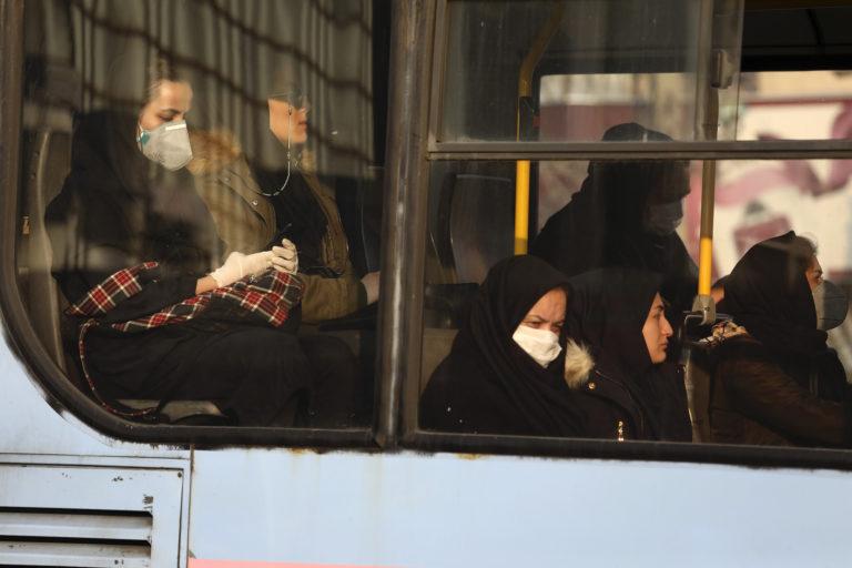 Woman, wearing face masks, travel on a public bus in a street in western Tehran, Iran, Saturday, Feb. 29, 2020. (Vahid Salemi/AP Photo)