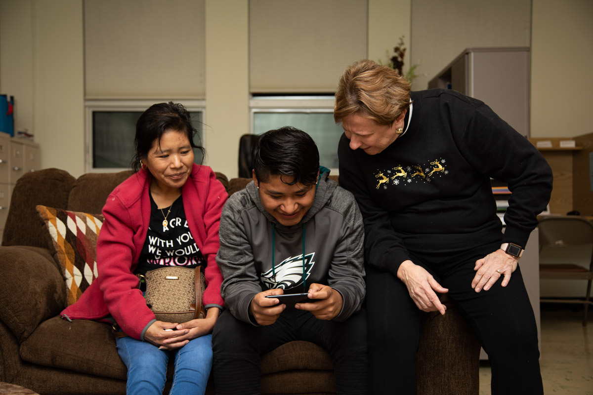 Fredy and Margarita with Sue Marshall at the King Street Ministry Center in Chambersburg, Pa. (Jeffrey Stockbridge for Keystone Crossroads)
