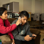 Fredy Garcia Morales and his mom Margarita talk to his sisters on the phone while sitting in the King Street Ministry Center in Chambersburg, Pa. (Jeffrey Stockbridge for Keystone Crossroads)