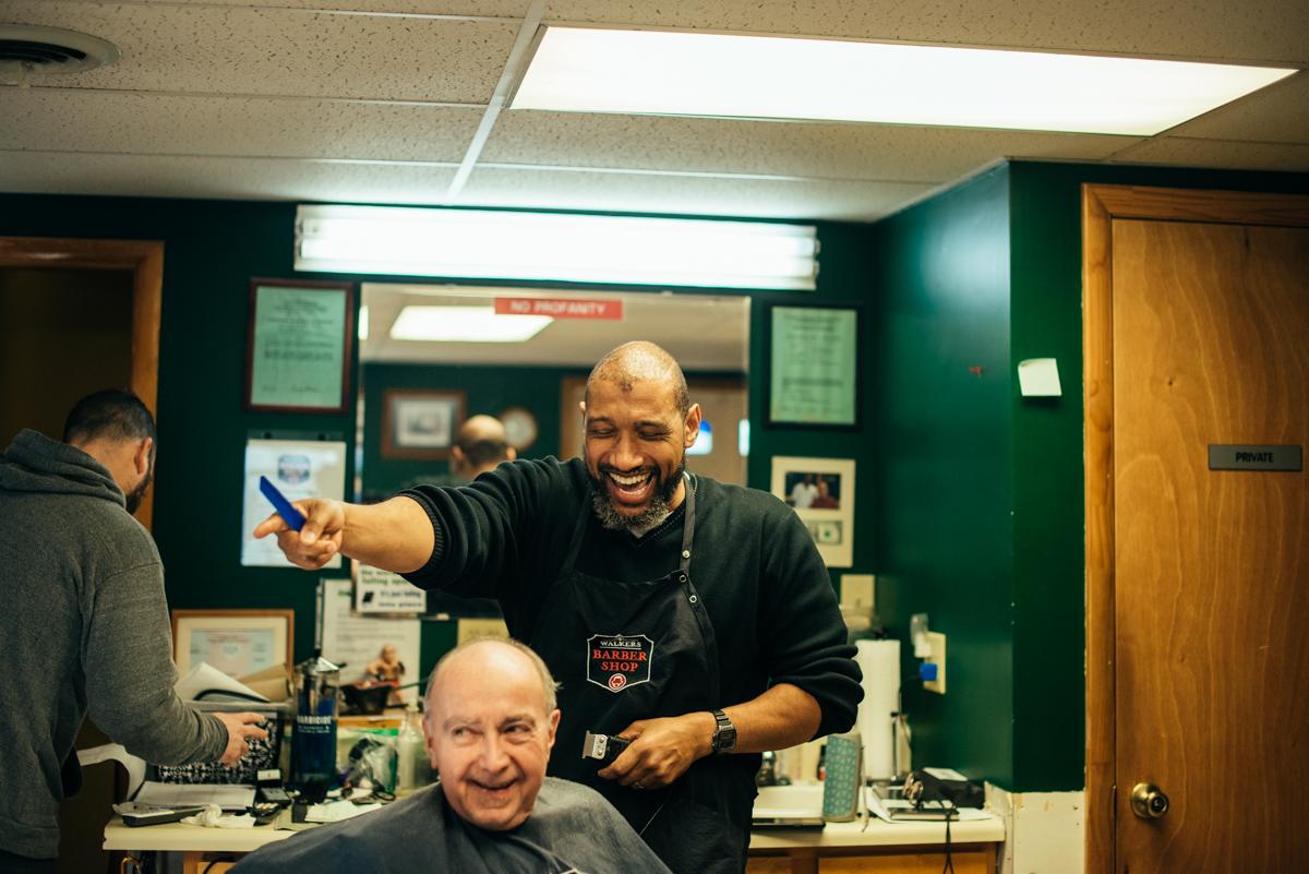 Lance Walker laughs while giving customer Tom Buckus a haircut. (Dani Fresh for Keystone Crossroads)