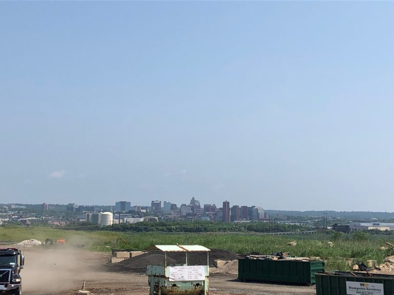 The skyline of Wilmington looms in the background of the Waste Management Inc. landfill south of the city. (Cris Barrish/WHYY)