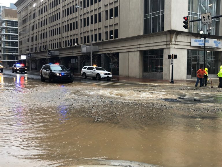 Public works crews were analyzing the water main break and city police blocked off access to the gusher. (Cris Barrish/WHYY News)