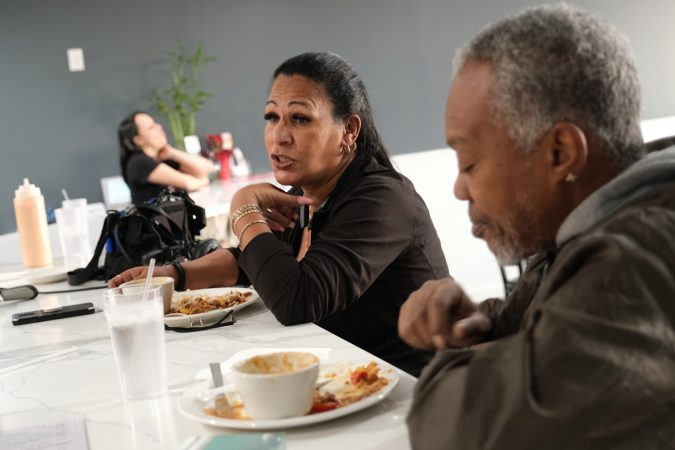 Iris Batista, left, of Mount Penn, talks while seated next to James Porter, right, at Mi Casa Su Casa in Reading, Pennsylvania. (Matt Smith for Keystone Crossroads)