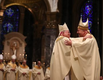Archbishop Charles J. Chaput (left) embraces Archbishop Nelson J. Pérez (right) during his installation at the Cathedral Basilica of Saints Peter and Paul in Philadelphia on February 18, 2020. (Pool photo/ by David Maialetti/The Philadelphia Inquirer)