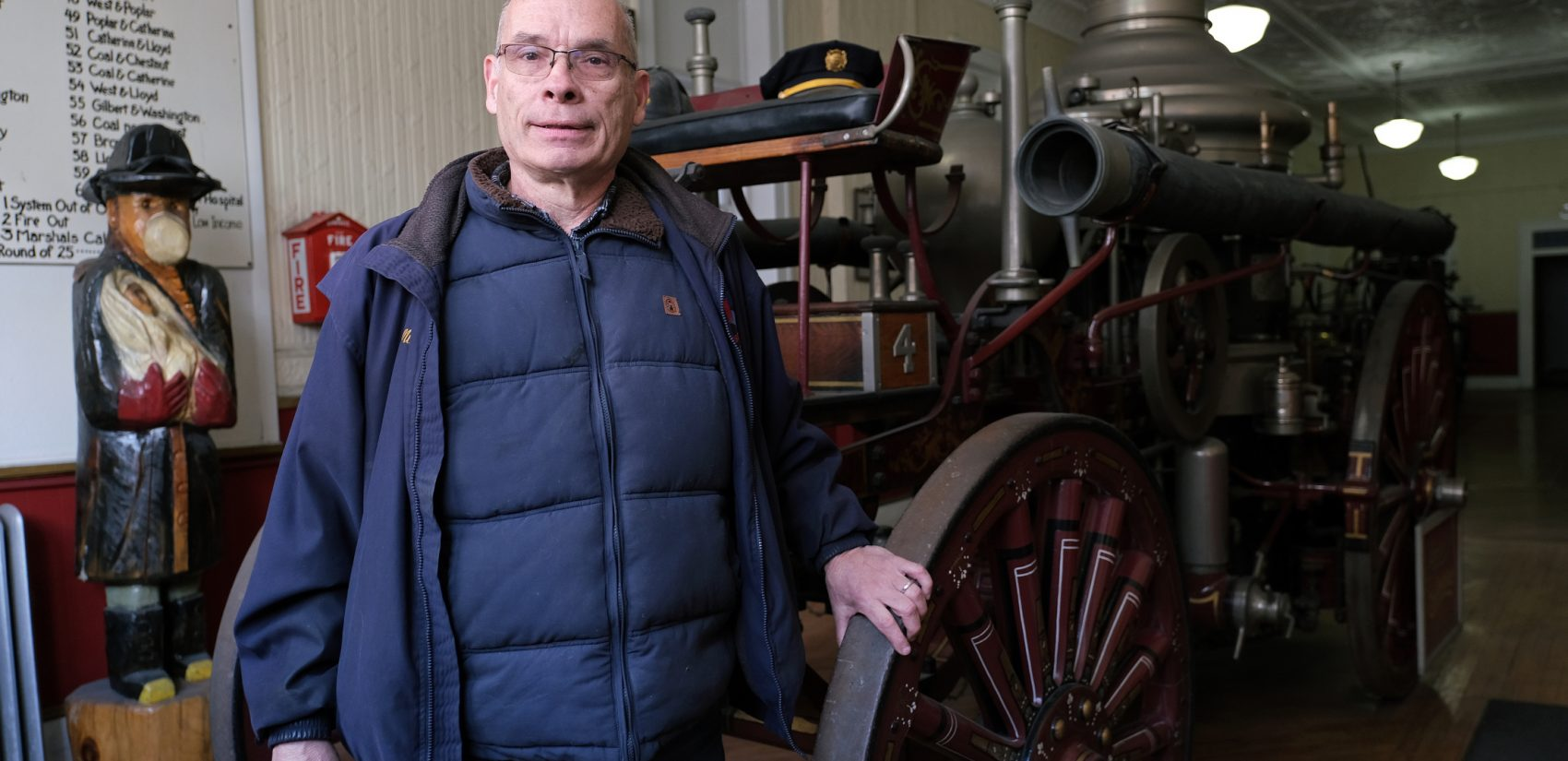 Veteran firefighter Mike Kitsock stands by a 1909 Ahrens Continental steam fire engine at the Schuylkill Historical Fire Society in Shenandoah, Pennsylvania. (Matt Smith for Keystone Crossroads)