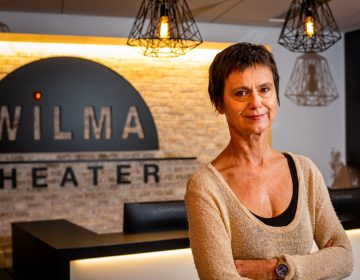 Blanka Zizka stands in front of a Wilma Theater sign