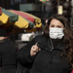 A woman, who declined to give her name, wears a mask in New York out of concern for the newly emerged coronavirus. (Mark Lennihan/AP Photo)