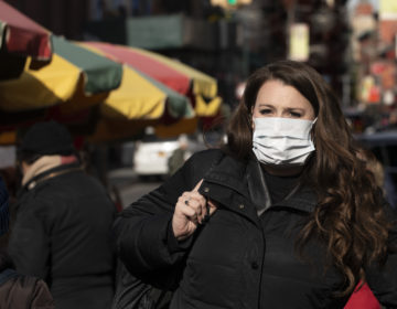 A woman, who declined to give her name, wears a mask in New York out of concern for the coronavirus. Experts say the masks do not necessarily help prevent the spread of the virus. (Mark Lennihan/AP Photo)